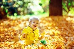 Mała szczęśliwa chłopiec w żółtej kurtce bawić się z liśćmi Fotografia Stock