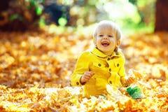 Mała szczęśliwa chłopiec w żółtej kurtce bawić się z liśćmi Zdjęcie Royalty Free