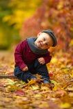 Mała szczęśliwa dziecko chłopiec siedzi w parku na tle kolorowy au obrazy stock