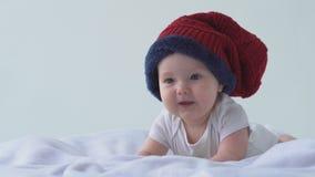 mała szczęśliwa Dziecko kłaść na śmiechach i łóżku w kapeluszu Biały tło zbiory