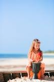 Mała szczęśliwa dziewczyna bawić się afrykanów bębeny Uroczy dzieciak ma zabawę z krajowym afrykaninem bębni na biel plaży Fotografia Stock