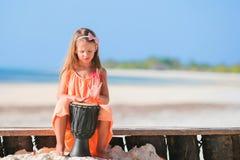 Mała szczęśliwa dziewczyna bawić się afrykanów bębeny Uroczy dzieciak ma zabawę z krajowym afrykaninem bębni na biel plaży Zdjęcia Royalty Free