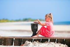 Mała szczęśliwa dziewczyna bawić się na afrykańskich bębenach Uroczy dzieciak ma zabawę z krajowym afrykaninem bębni na biel plaż Zdjęcie Stock