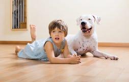 Mała szczęśliwa dziewczyna na podłoga z psem zdjęcie royalty free