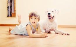 Mała szczęśliwa dziewczyna na podłoga z psem zdjęcia royalty free