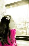Mała szczęśliwa dziewczyna patrzeje przez okno fotografia stock