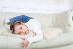 Mała szczęśliwa dziewczyna w cajgach kłama na białej skóry kanapie Fotografia Stock