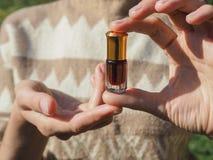 Mała szklana butelka agarwood olej w żeńskich palmach olej czujący Fotografia Stock