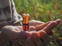 Mała szklana butelka agarwood olej w żeńskich palmach olej czujący Zdjęcia Royalty Free