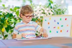 Mała szkolna dzieciak chłopiec trzyma wosk kredki z szkłami Obraz Stock
