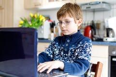 Mała szkolna dzieciak chłopiec z szkłami robi preschool pracie domowej na komputerze Dziecko ma zabawę z uczenie na komputeru oso Fotografia Royalty Free