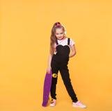 Mała szkolna dziewczyna pozuje z deskorolka i hełmofonami Zdjęcie Royalty Free