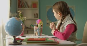 Mała Szkolna dziewczyna Robi pracie domowej przy stołem na słonecznym dniu w domu zbiory wideo