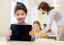 Mała szkolna dziewczyna z pastylka komputerem osobistym nad sala lekcyjną Zdjęcia Royalty Free