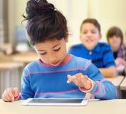 Mała szkolna dziewczyna z pastylka komputerem osobistym nad sala lekcyjną Zdjęcie Royalty Free