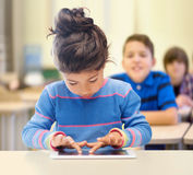 Mała szkolna dziewczyna z pastylka komputerem osobistym nad sala lekcyjną Obraz Stock
