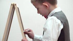 Mała szkolnej chłopiec writing ostrość kredowa deska, dziecko ostrożny jego aktywność zbiory wideo