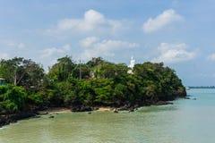 Mała tropikalna wyspa zakrywająca z zieloną roślinnością w ciepłym morzu fotografia stock