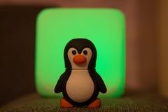 Mała Tux zabawka przy Zamazanym Zielonym tłem Obrazy Royalty Free