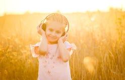 Mała uśmiechnięta blond dziewczyna listenning muzyka zdjęcia royalty free