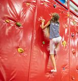 Mała uśmiechnięta blond dziewczyna stoi blisko czerwonej pięcie ściany w sztuka pokoju fotografia royalty free