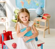 Mała uśmiechnięta blond dziewczyna trzyma błękitną książkę w szkolnej klasie Zdjęcie Stock