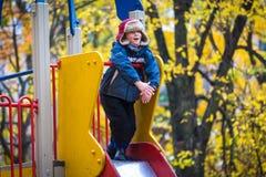 Mała uśmiechnięta chłopiec pozycja na obruszeniu, jesień sezon Zdjęcia Royalty Free