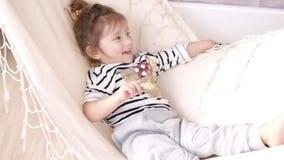 Mała uśmiechnięta dziewczyna chłodzi i huśta się na białym hamaku _ zbiory