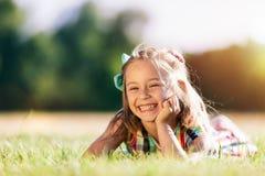 Mała uśmiechnięta dziewczyna kłaść na trawy polu w parku zdjęcie royalty free