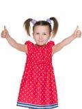 Mała uśmiechnięta dziewczyna trzyma jej aprobaty Zdjęcie Royalty Free