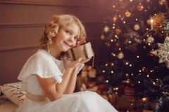 Mała uśmiechnięta dziewczyna z boże narodzenie nowego roku prezenta pudełkiem obrazy royalty free