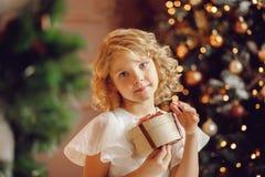 Mała uśmiechnięta dziewczyna z boże narodzenie nowego roku prezenta pudełkiem zdjęcie stock