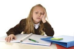 Mała uczennica smutna i zmęczony patrzeje przygnębiony cierpienie stres przytłaczający ładunkiem praca domowa Zdjęcia Royalty Free