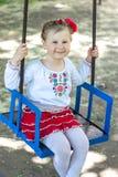 Mała ukraińska dziecko dziewczyna ma zabawę na huśtawce Zdjęcia Stock