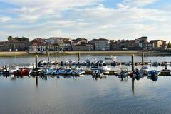 Mała wioska rybacka z molem i łodziami Plaża, schronienie i deptak z drzewami, Zmierzchu światło, niebieskie niebo z chmurami Cam zdjęcia stock