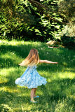 Mała wiruje dziewczyna w błękitnej sukni w lato ogródzie Zdjęcia Royalty Free