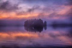 Mała wyspa po środku jeziora w mgle Obrazy Royalty Free