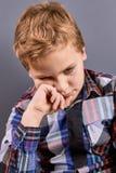 Mała zadumana chłopiec patrzeje w dół Fotografia Royalty Free