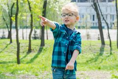 Mała zdziwiona chłopiec w szkłach pokazuje gdzieś z palcem w parku obraz stock
