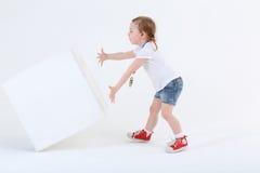 Mała zdziwiona dziewczyna w skrótach pcha wielkiego białego sześcian zdjęcie royalty free