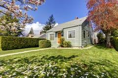 Mała zielonego domu powierzchowność z wiosen kwitnącymi drzewami. Obraz Stock