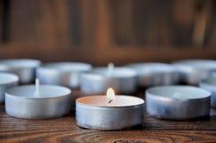 Małe świeczki - pigułka stojak na drewnianym stole fotografia stock