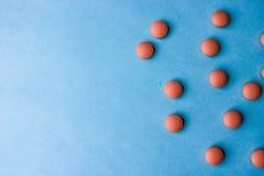 Małe żółte pomarańczowe piękne medyczne pharmaceptic round pigułki, witaminy, leki, antybiotyki na błękitnym tle, tekstura fotografia stock