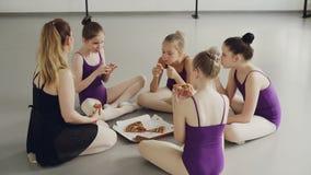 Małe żeńskie gimnastyczki jedzą pizzy obsiadanie na podłoga z ich nauczycielem po trenować, opowiadać i śmiać się, zbiory