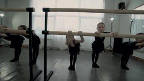 Małe baleriny są rozciągliwością na baletniczym barre i uśmiechem zbiory