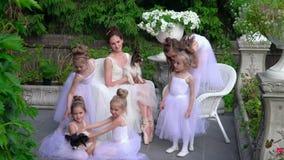 Małe baleriny wraz z nauczycielem siedzą na białych krzesłach rekreacyjny teren zbiory wideo