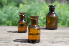 Małe brąz butelki na drewnianej desce i zielonej trawie obraz royalty free