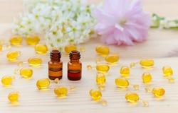 Małe brąz butelki z neroli i róży istotnymi olejami, złociste kapsuły naturalny kosmetyk, kwiaty kwitną na Obrazy Stock