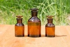 Małe brown butelki dalej booden deskę i trawy obraz stock