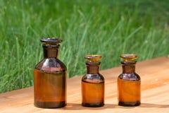 Małe brown butelki dalej booden deskę i trawy Fotografia Royalty Free